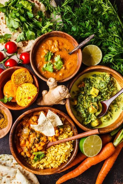 Dal, palak paneer, curry, reis, chapati, chutney in holzschalen auf dunklem tisch. Premium Fotos