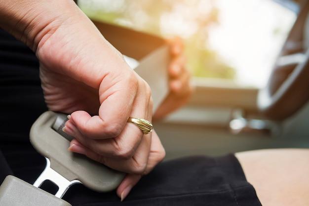 Dame, die autosicherheitsgurt vor dem fahren, nah an der gürtelschnalle, sicheres antriebskonzept setzt Kostenlose Fotos