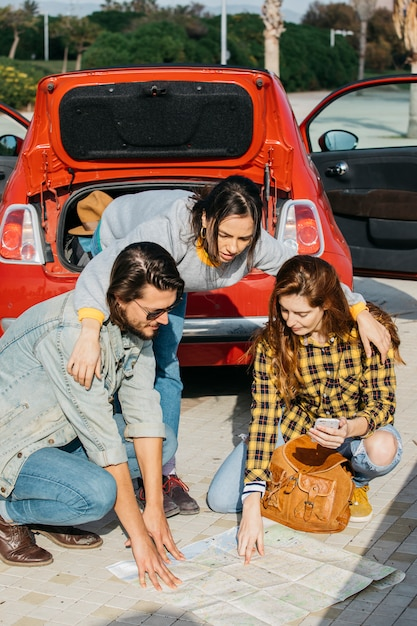 Dame, die frau mit rucksack und smartphone nahe mann umarmt und karte nahe auto betrachtet Kostenlose Fotos