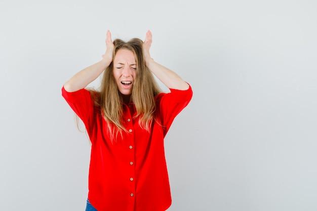 Dame im roten hemd, das hände zum kopf hält und wehmütig aussieht, Kostenlose Fotos