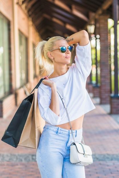Dame in der sonnenbrille, die taschen auf schulter hält Kostenlose Fotos