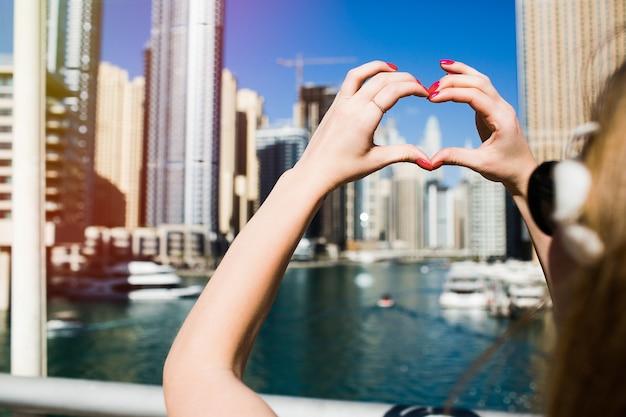 Dame mit roten nägeln zeigt herz mit ihren fingern vor wolkenkratzern von dubai Kostenlose Fotos