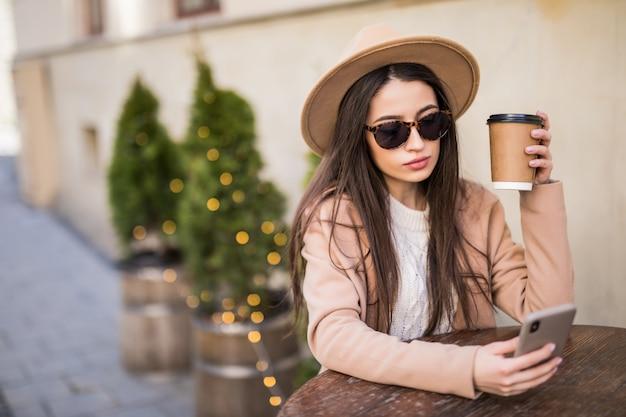 Dame sitzt auf dem tisch im café kleider in freizeitkleidung dunkle sonnenbrille mit kaffeetasse und telefon Kostenlose Fotos