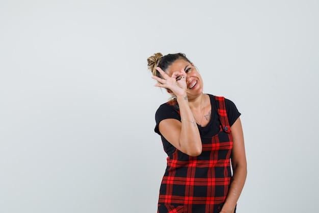 Dame zeigt ok zeichen auf auge im trägerkleid und schaut fröhlich, vorderansicht. Kostenlose Fotos