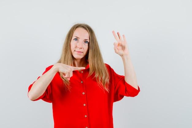 Dame zeigt zur seite, zeigt ok zeichen im roten hemd und sieht selbstbewusst aus. Kostenlose Fotos