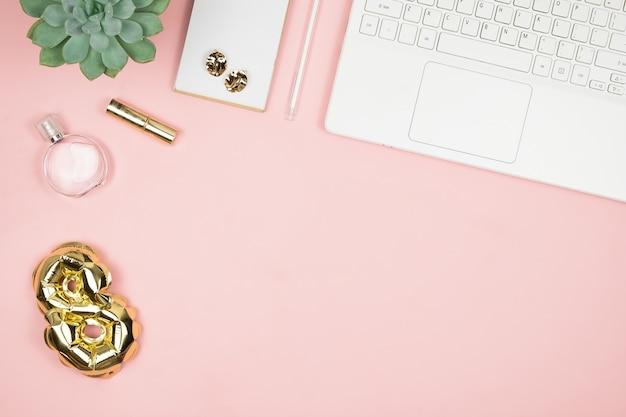 Damen-desktop mit laptop, parfum, goldfolienballon 8 und copyspace. draufsicht. alles gute zum tag der frauen. 8. märz glückwunsch. Premium Fotos