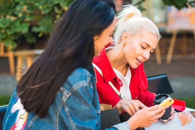 Damen, die smartphone auf bank im park verwenden Kostenlose Fotos