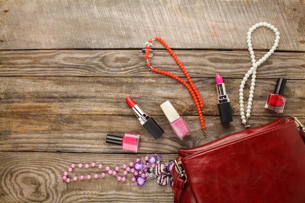 Damenaccessoires: kosmetiktasche, halskette, nagellack, lippenstift. Premium Fotos