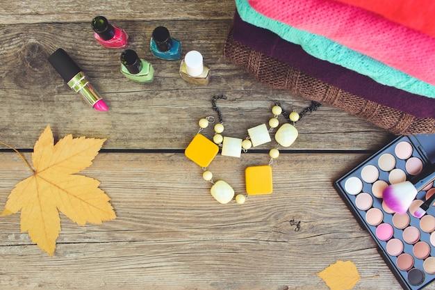 Damenbekleidung und kosmetik auf hölzernen hintergrund Premium Fotos