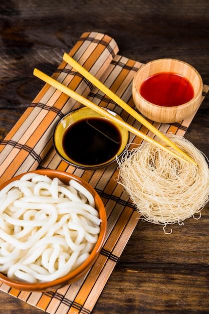 Dampft udon-nudeln; reisnudeln und saucen mit hölzernen essstäbchen über der platzmatte gegen holztisch Kostenlose Fotos