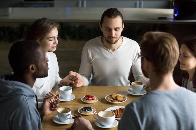 Dankbare gemischtrassige freunde, die zusammen am cafétisch sitzen, gnade sagend Kostenlose Fotos