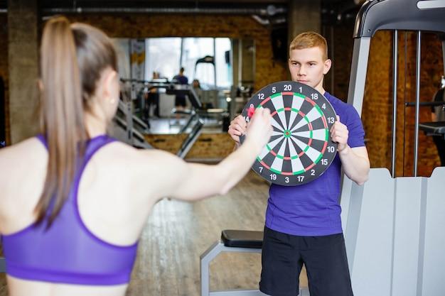 Dart spielen im fitnessstudio. Premium Fotos