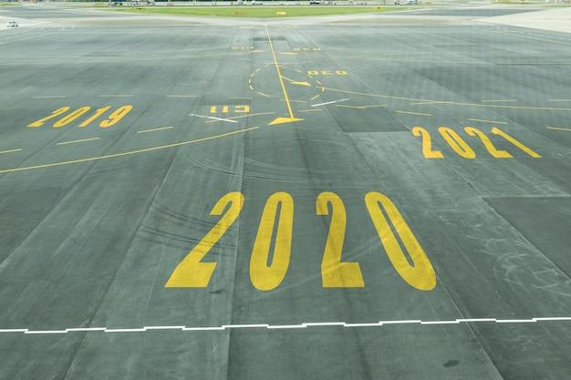 Das 2020-nummernschild auf der landebahn des flughafens zeigt den bevorstehenden neujahrsempfang. Premium Fotos