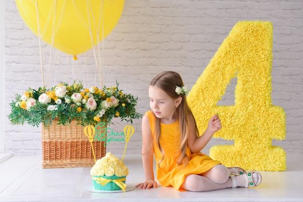Das 4-5-jährige geburtstagskind feiert geburtstag in einem dekorierten, stilisierten studio mit der nummer 4 und einem großen ballon. gelber stil. Premium Fotos