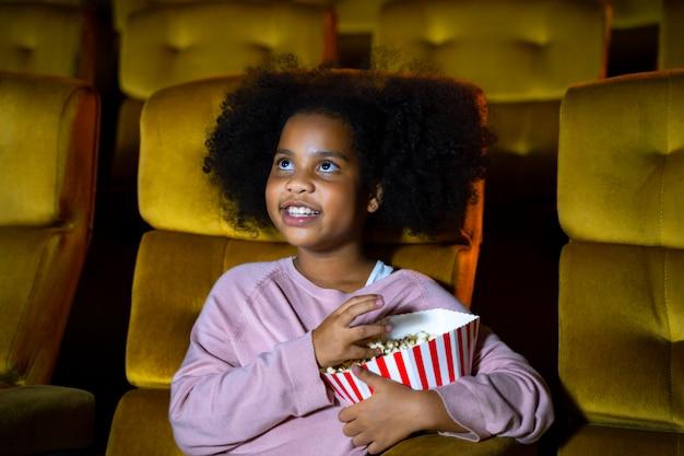 Das afrikanische mädchen sitzt und schaut sich das kino an den kinositzen an. die gesichter fühlen sich glücklich und genießen. Premium Fotos