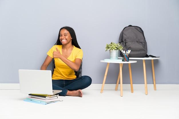 Das afroamerikanerjugendlich-studentenmädchen mit dem langen umsponnenen haar, das auf dem boden gibt daumen sitzt, up geste Premium Fotos
