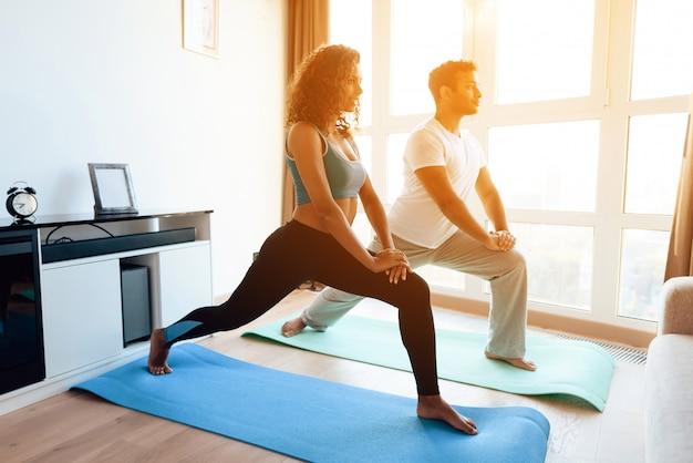 Das afroamerikanerpaar, das yoga tut, trainiert zu hause Premium Fotos