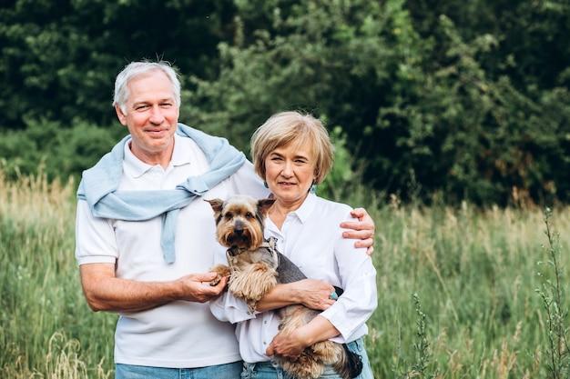 Das alte ehepaar geht in der natur spazieren, händchen