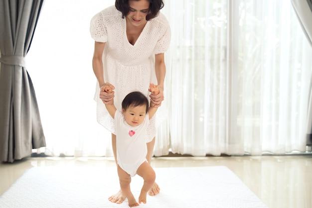 Das asiatische baby, das erste schritte unternimmt, gehen vorwärts mit mutterunterstützung. Premium Fotos