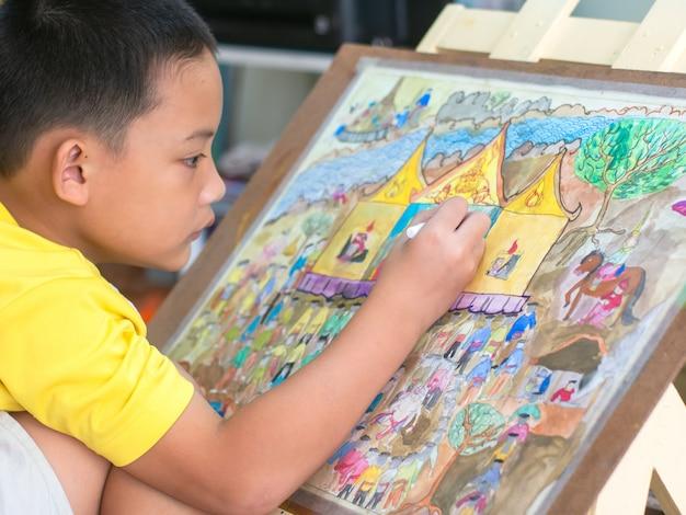 Das asiatische kind, das seine kunst-, aquarell- und bleistiftfarbe auf papier zeichnet und malt. Premium Fotos