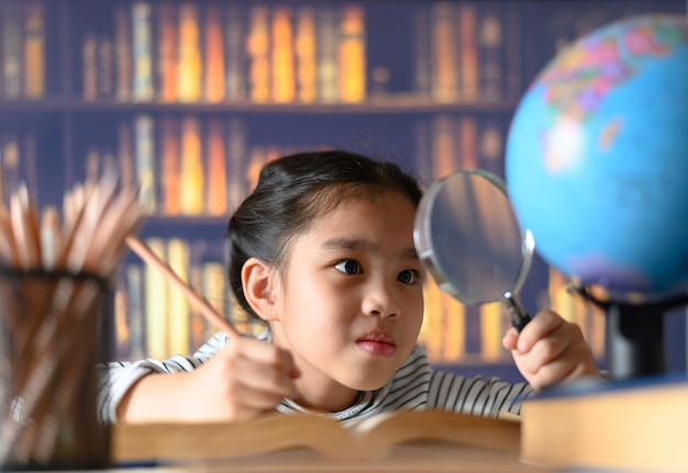Das asiatische kindermädchen, das fleißig ist, sitzt zuhause an einem schreibtisch. kind lernt zu hause Premium Fotos
