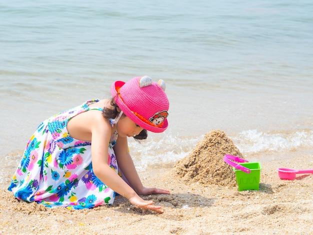 Das asiatische nette mädchen, das bunte kleider und rosa hut trägt, spielen sand auf dem strand. Premium Fotos
