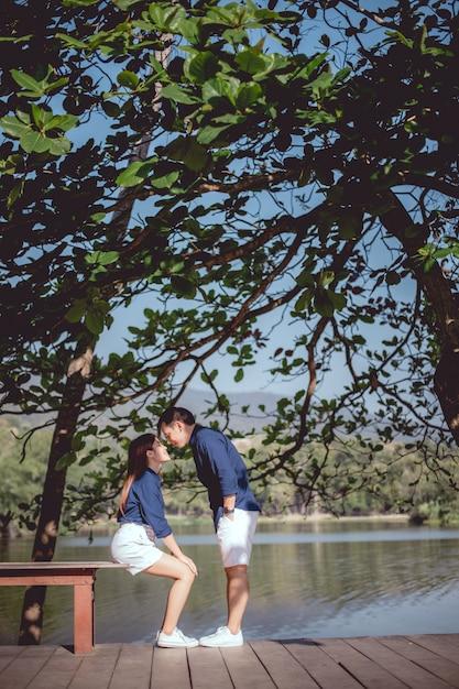 Das asiatische paar wird zusammen im park neben dem see küssen. Premium Fotos