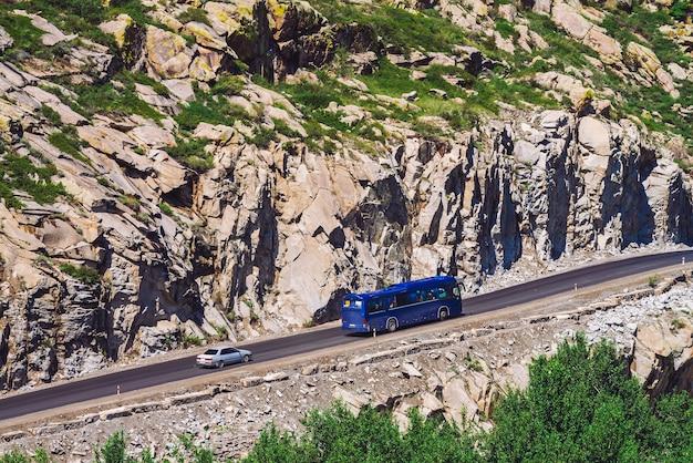 Das auto fährt entlang der highland highway über den abgrund in der nähe einer riesigen felsigen klippe Premium Fotos
