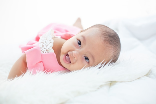 Das baby ist glücklich auf dem bett. Kostenlose Fotos