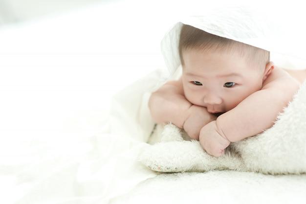 Das baby starrt nach vorne auf ein weißes bett mit weißem hintergrund. Premium Fotos