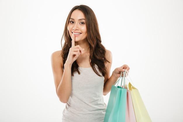 Das bild der flirtfrau einkaufssätze halten und fragend halten geheimnis mit dem setzen des fingers auf die lippen, lokalisiert über weißer wand Kostenlose Fotos