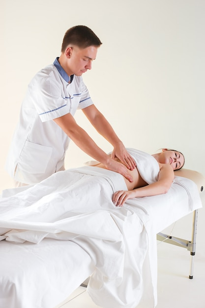 Das bild der schönen frau im massagesalon und in den männlichen händen auf ihrem körper Kostenlose Fotos