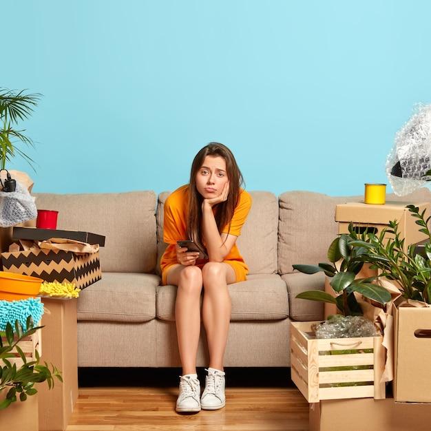 Das bild einer unzufriedenen europäischen frau sitzt alleine auf dem sofa im wohnzimmer, fühlt sich einsam und frustriert, hält ein modernes mobiltelefon, umgeben von pappkartons nach dem umzug, hat viel zu tun Kostenlose Fotos