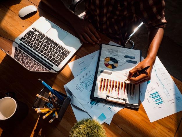 Das bild eines business-designers hält einen stift in der hand, um ein diagramm für ein erfolgreiches anlageergebnis zu schreiben. Premium Fotos