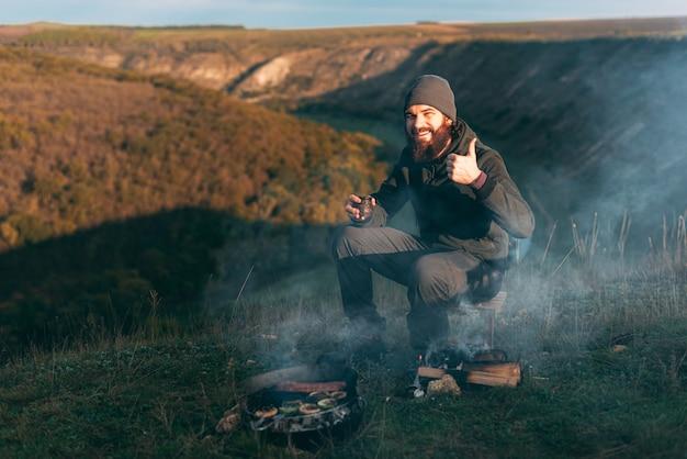 Das bild eines jungen mannes mit bart sitzt morgens in der nähe eines grills mit gemüse und würstchen auf einem feld Premium Fotos