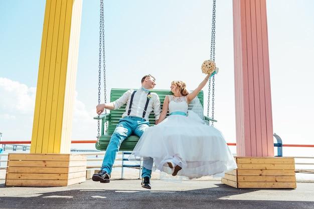 Das brautpaar reitet auf einer schaukel Premium Fotos