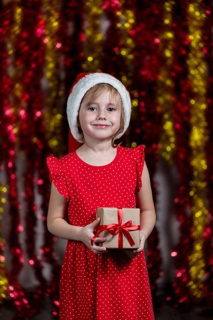 Das entzückende kleine mädchen in der weihnachtsmütze hält neujahrsgeschenk mit träumendem gesichtsausdruck. Premium Fotos