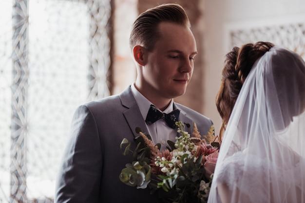 Das erste treffen. der bräutigam kommt mit einem blumenstrauß ins zimmer der braut. sie umarmen und küssen sich. rosa hochzeitskleid, grauer anzug und stilvoller blumenstrauß. zimmer im marokkanischen stil. Premium Fotos