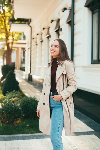 Das foto einer jungen frau, die lächelt, schaut weg nahe einem gebäude Premium Fotos