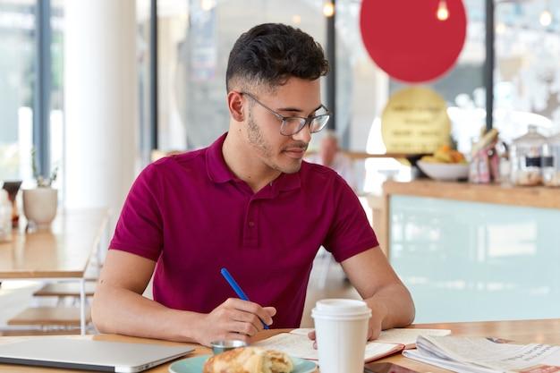 Das foto eines männlichen studenten gemischter rassen schreibt die notwendigen informationen in den notizblock der tageszeitung, erstellt einen ähnlichen artikel, sitzt drinnen gegen das innere eines cafés, trinkt kaffee, lernt drinnen Kostenlose Fotos