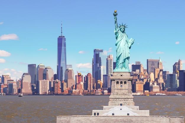 Das freiheitsstatue mit dem one world trade building center über dem hudson river und dem new yorker stadtbildhintergrund, marksteine von unterem manhattan new york city. Premium Fotos