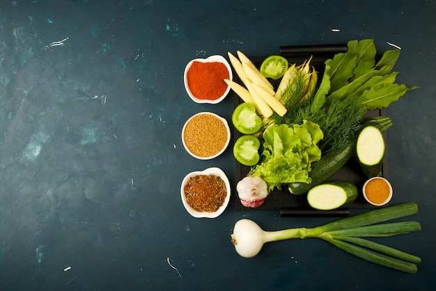 Das gemüse im kasten auf dem stein ein dunkel. junge grüne zwiebel knoblauch zucchini helle gewürze lagern in einem holztablett mit griffen auf einem dunkelen beschaffenen. Premium Fotos