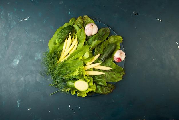 Das gemüse im kasten auf dem stein ein dunkel. junge grüne zwiebel knoblauch zucchini helle gewürze sind in einer holzkiste mit seilgriffen auf einem dunkelen strukturierten. Premium Fotos