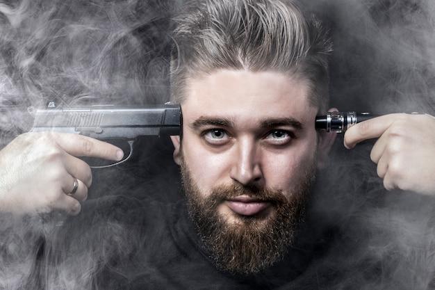 Das gesicht eines mannes mit einer pistole an der schläfe und auf der anderen seite eine elektronische zigarette, umgeben von rauch, rauchen tötet das konzept, nahaufnahme Premium Fotos