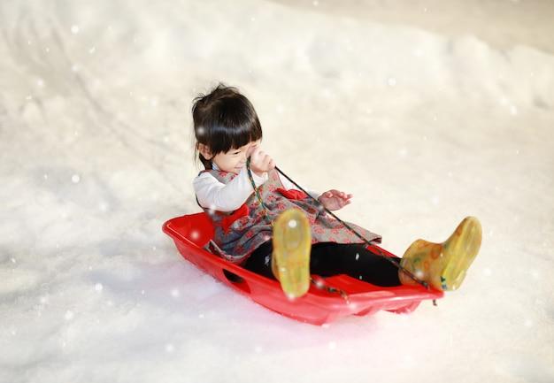 Das glückliche kleine mädchen, das eine rot - graue jacke trägt, hat spaß im schnee Premium Fotos