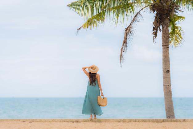 Das glückliche lächeln der jungen asiatischen frauen des schönen porträts entspannen sich um strandseeozean Kostenlose Fotos