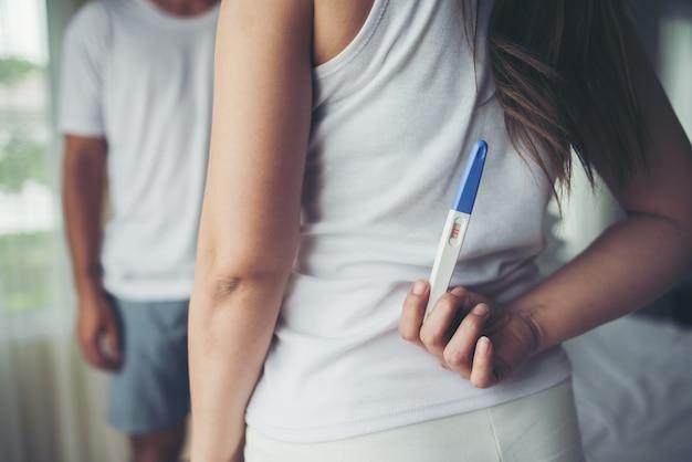 Das glückliche paar, das nach lächelt, finden positiven schwangerschaftstest im schlafzimmer heraus Kostenlose Fotos