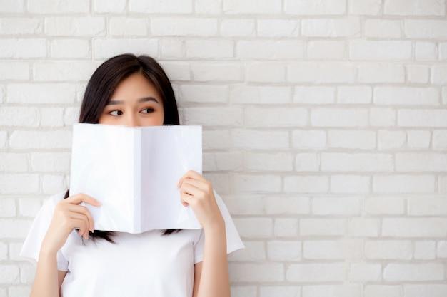 Das glückliche verstecken der schönen asiatischen frau des porträts hinter öffnen das buch Premium Fotos