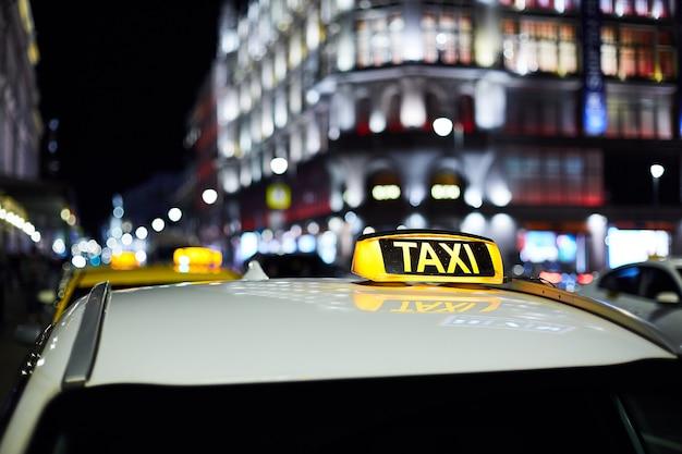 Das große taxischild auf der nachtstadt Premium Fotos