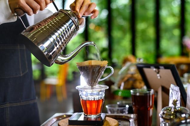 Das heiße wasser des barista-frauenmädchens bereitet gefilterten kaffee zu Premium Fotos